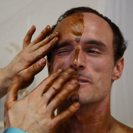 Процесс нанесения тонального крема на кожу спортсмена