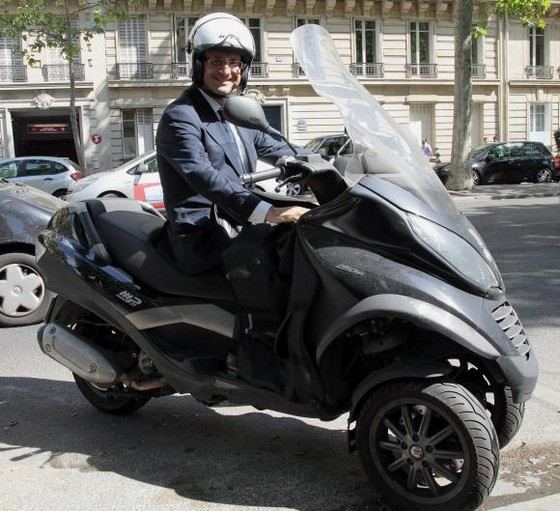 Francois Hollande in the helmet on a scooter