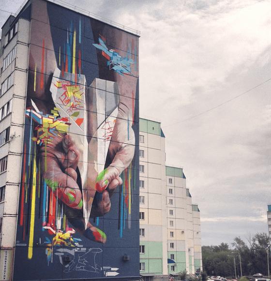 Картина на фасаде жилого дома. Изображены руки, поймавшие самолетик