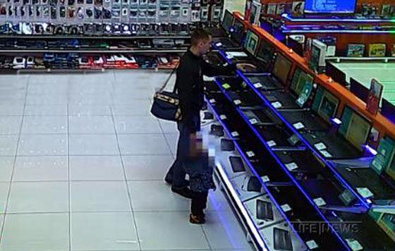 Мужчина взял ноутбук с витрины и быстро спрятал его под свитер
